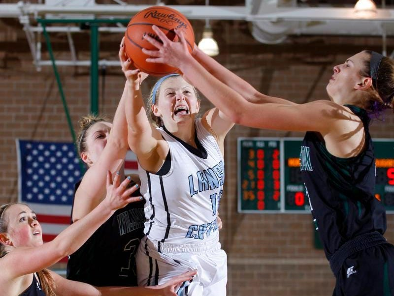 Lansing Catholic's Becka Poljan, center, and Williamston's Renee Sturm, right, Halle Wisbiski, left, and Allison Peplowski fight for a rebound Wednesday at Williamston High School.