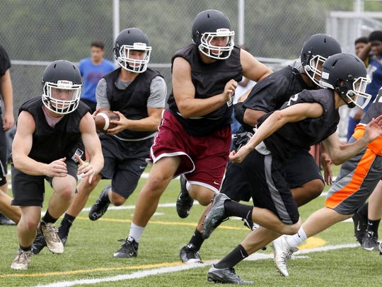 Elmira High School football players run a play Aug.