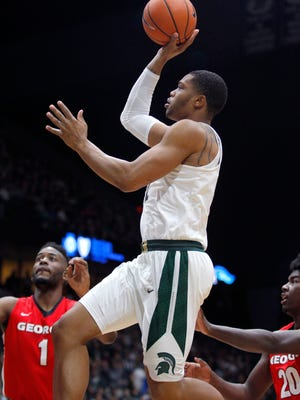 Michigan State's Miles Bridges, center, puts up a runner against Georgia's Yante Maten (1) and Rayshaun Hammonds (20) during the first half of an NCAA college basketball exhibition game, Sunday, Oct. 29, 2017, in Grand Rapids.