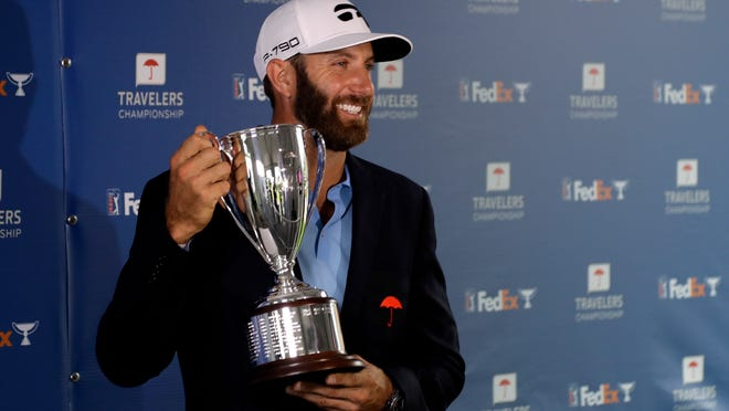 Dustin Johnson poses with the trophy after winning the Travelers Championship golf tournament at TPC River Highlands, Sunday, June 28, 2020, in Cromwell, Conn.