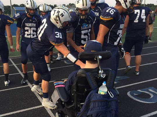 Matt DeRiggi hangs on the sidelines with Toms River North football players