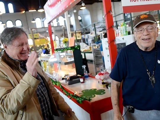 John Wills, a longtime customer at Henry's Ham in Central Market, jokes around with former owner, Fred Henry, who had recently sold the stand.