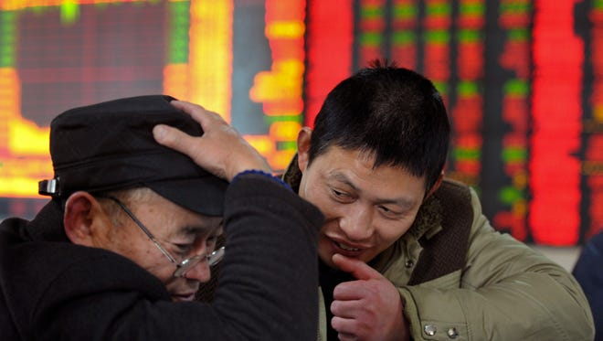 Investors check on stock prices Dec. 4 at a brokerage house in Fuyang in central China's Anhui province.