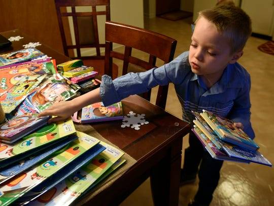 Conner Keiper, 8, goes through the books he's collected the afternoon of Monday, Dec. 18 in the kitchen of his Chambersburg home. Keiper is donating the toys he would normally get for his birthday on Dec. 17 to children in hospitals.
