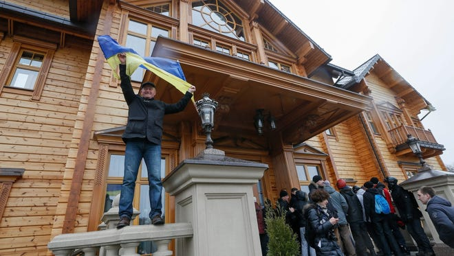 A Ukrainian waves a national flag as he poses in front of one of the main buildings in the residence of Ukrainian President Viktor Yanukovych near Kiev on Feb. 22.