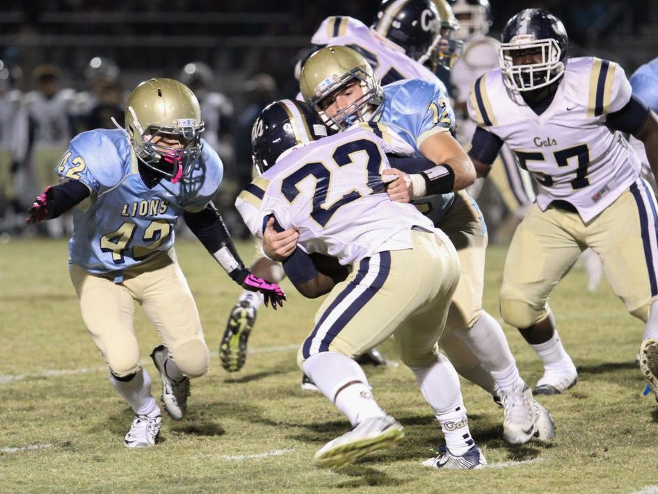 Daniel linebacker Chris Barnes (12) tackles Braxton Gambrell (22) of Seneca Friday night at Daniel High.