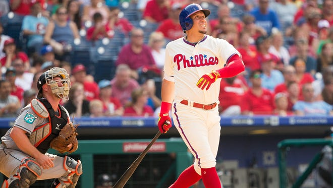 Phillies second baseman Asdrubal Cabrera hits a two-run homer in front of Marlins catcher Bryan Holaday during the eighth inning Sunday.