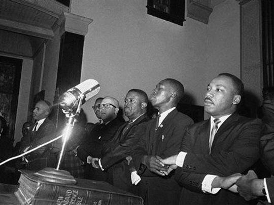 In this March 9, 1965, file photo, Dr. Martin Luther King Jr. joins hands with other African American leaders singing 'We Shall Overcome' at a church rally in Selma, Ala. Third to the left of King is the Rev. Jesse L. Douglas.