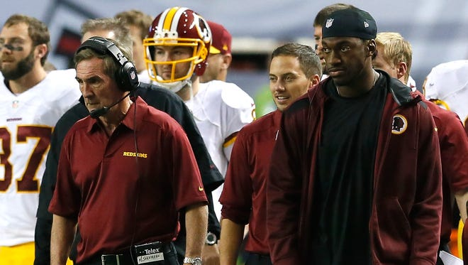 Redskins QB Robert Griffin III, right, and former coach Mike Shanahan had little to smile about at the end of the 2013 season.