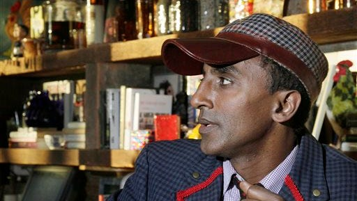 This file photo shows Chef Marcus Samuelsson, owner of the Red Rooster, at the restaurant in New York. Growing up in Sweden, Samuelsson learned many lessons that would follow him into the kitchen as an adult, from how to smoke mackerel to the best technique for forming meatballs. But the one that stuck with him the most came from his father and was about skin color, not culinary skill. Samuelsson, who was born in Ethiopia and adopted by a Swedish family after his mother died, said his father taught him early that life in the restaurant industry would be different as a black chef from Africa.