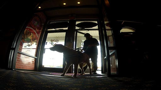 """Munger, a psychiatric service dog, """"clears"""" the area as Joe Aguirre enters a restaurant in Fayetteville, N.C. The 3-year-old Golden Retriever helps the Army veteran cope with his post-traumatic stress disorder."""