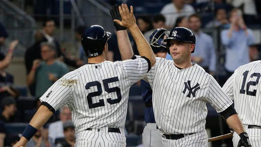 New York Yankees' Brian McCann, right, is greeted at home plate by Mark Teixeira (25) after hitting a two-run home run against the Tampa Bay Rays during the second inning of a baseball game, Friday, April 22, 2016, in New York. (AP Photo/Julie Jacobson)