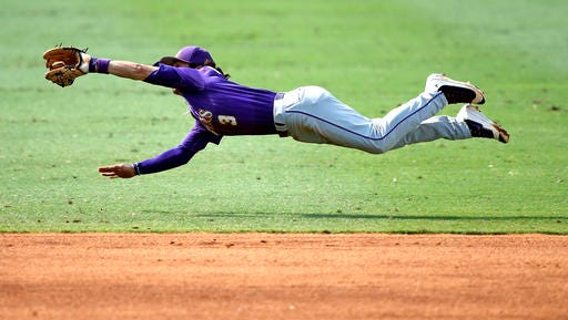 LSU's Kramer Robertson (3) dives to grab a line drive by Rice's Ford Proctor for the out to end the second inning of an NCAA college baseball tournament regional game in Baton Rouge.