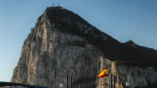 FILE- In this Wednesday, March 1, 2017 file photo, a Spanish flag flies on top of the customs house on the Spanish side of the border between Spain and the British overseas territory of Gibraltar with the Rock as a background, in La Linea de la Concepcion, Southern Spain. The EU's roadmap on Brexit negotiations leaves the U.K. and Spain to discuss what agreements will apply to Gibraltar, a dialogue in which Madrid could have the upper hand.