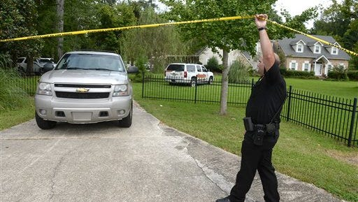 In an Aug. 27, 2014 photo, an Iberville Sheriff's deputy allows an official vehicle to leave the crime scene where investigators work at the home of TV personality Scott Rogers, who was shot and killed there, in St. Gabriel, La. When Rogers, 52, was shot to death in August by his son-in-law Matthew Hodgkinson, who authorities say then took his own life, their adopted hometown was stunned. Hodgkinson, was also Rogers' longtime lover, whose marriage to Rogers' daughter was an immigration sham, Iberville Parish Sheriff Brett Stassi later said. More shocking was the reason authorities gave for what they called a murder-suicide pact: Rogers was under federal investigation, and a dark secret he thought he had left behind years earlier in England was likely to resurface.