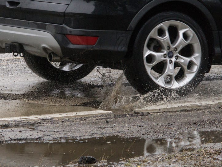 Water fills many potholes, hiding the depth of the