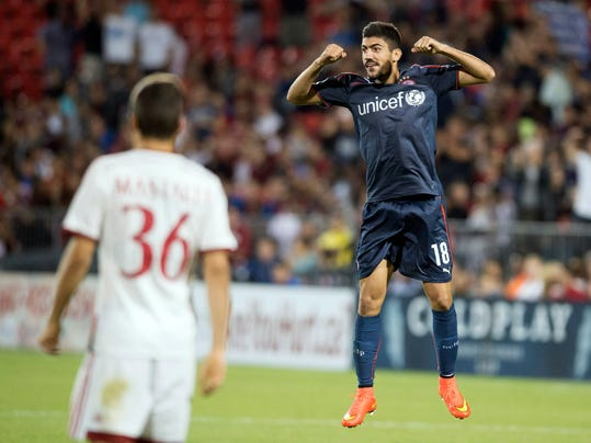 Olympiacos' Andreas Bouchalakis, right, celebrates his second-half goal in front of AC Milan's Alessandro Mastalli during an International Champions Cup soccer match at BMO Field in Toronto on Thursday, July 24, 2014.  (AP Photo/The Canadian Press, Darren Calabrese)