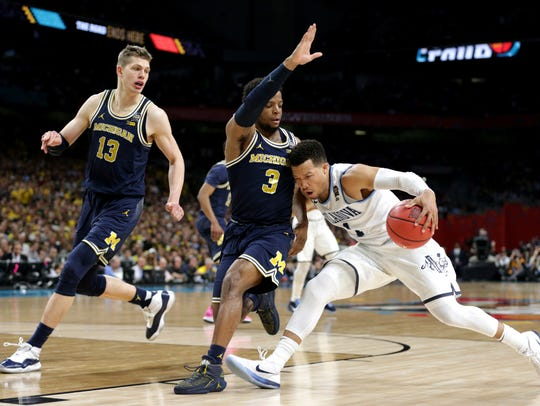 Michigan forward Moritz Wagner (13) and guard Zavier Simpson pressure Villanova guard Jalen Brunson during the first half Monday at the Alamodome in San Antonio.