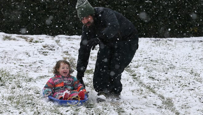 Ed Farruggia guides his 3-year-old daughter, Amelia, down a slope at Ault Park in Hyde Park, Saturday, March 24, 2018. A winter weather warning remains in effect until 2 a.m. Sunday for portions of Southeast Indiana, Northeast and Northern Kentucky and Southwest Ohio, including Hamilton County. Butler, Clermont, Brown, and Adams counties are under a winter storm advisory until 2 a.m. Sunday.