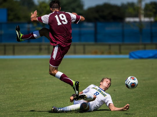 Delaware's Jaime Martinez (No. 8) makes a sliding tackle to take the ball away from Fordham's Christopher Bazzini (No. 19) in the first half of Delaware's 1-0 win over Fordham at Grant Stadium at the University of Delaware on Sunday afternoon.