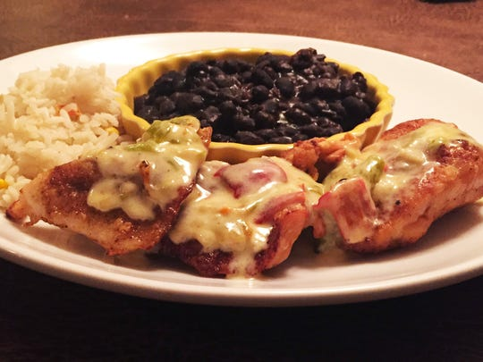 Chicken breast medallions ($15), lightly floured and pan fried, with a green chile cream sauce and spicy confetti rice and the house-made black beans.