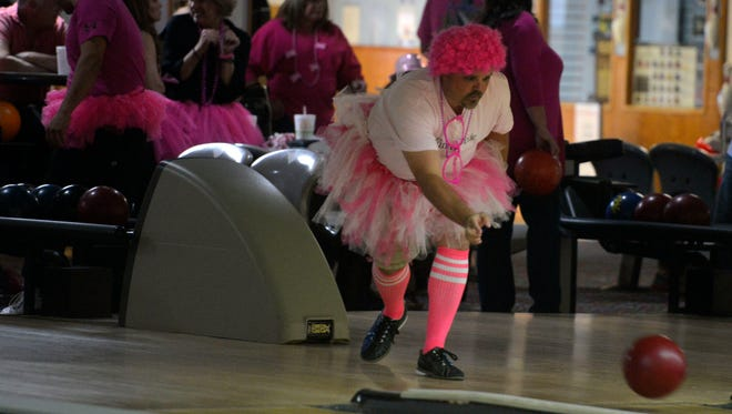 Blake McConkey guides his ball down the lane during a Breast Cancer Research Foundation Hot Pink Weekend bowling tournament at DeLuna Lanes.