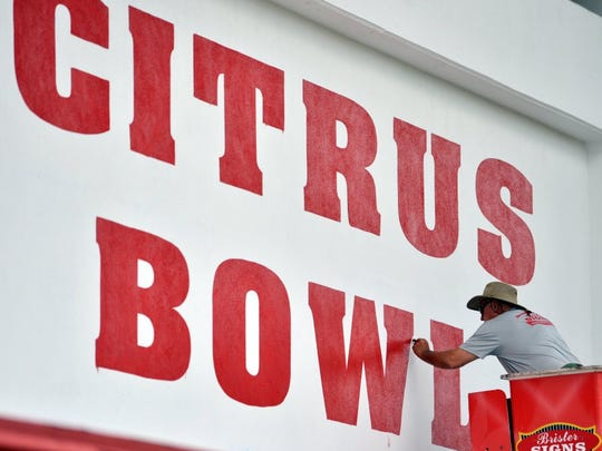 Buster Brister puts the final touches of paint on a sign at the Citrus Bowl on May 20, 2016 before the gates should have opened to the public for the spring football game between Vero Beach and Dwyer High School. The game was postponed until May 24, 2016 because of the threat of severe weather.