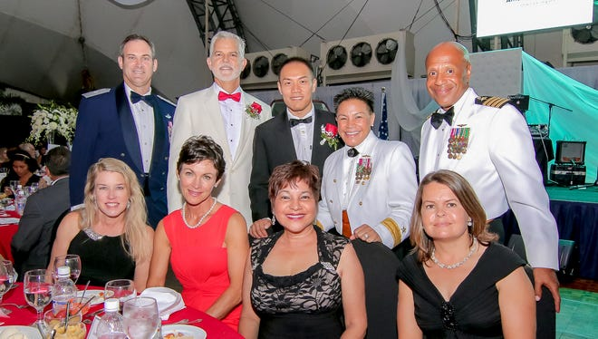 Standing from left, Brig. Gen. Andrew Toth, Jeff Jones, Marcos Fong, Rear Adm Babette Bolivar, and Captain Andy Anderson; sitting from left, Cheryl Toth, Jane Jones, Sen. Judy Won Pat, and Yolanda Anderson smile for the camera at the 15th annual Red Ball gala on Sept. 19, a fundraiser for the American Red Cross Guam Chapter.
