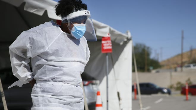 FILE - In this Oct. 26,2020, file photo, a medical worker stands at a COVID-19 state drive-thru testing site at UTEP, in El Paso, Texas. The U.S. has recorded about 10.3 million confirmed infections, with new cases soaring to all-time highs of well over 120,000 per day over the past week.