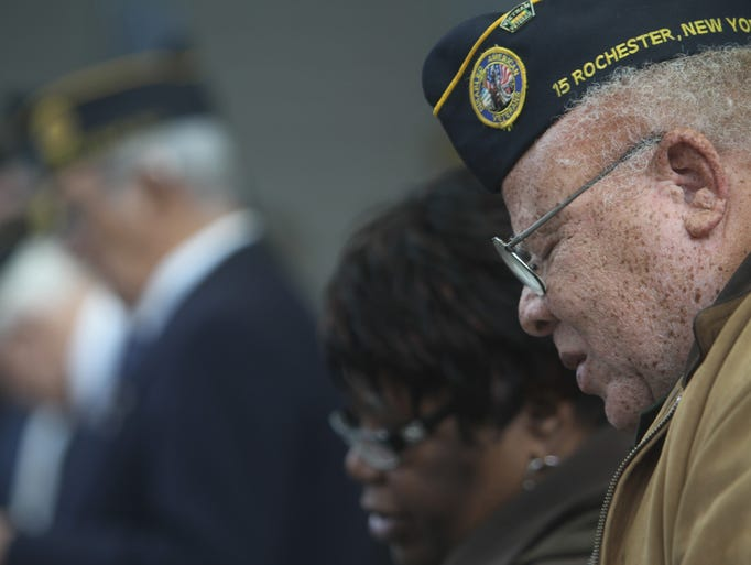 Thomas and Diane Nelson of Chili follow along to the music in the program during the Veterans Day service at the Rochester Community War Memorial  on Nov. 11, 2013. Thomas Nelson is with the Disabled American Veteran Chapter 15.