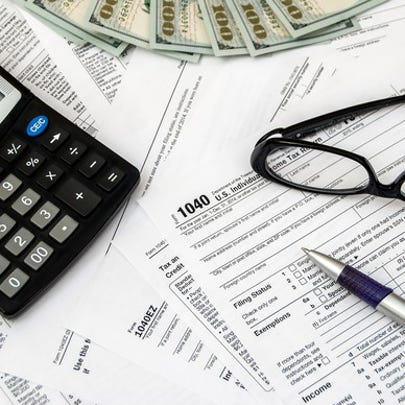 Calculator, pen, glasses, tax forms, and money on a flat surface piled in a disorganized fashion.