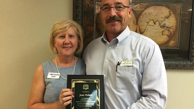 Joan Vickers, left, receives a plaque of appreciation from Wes Henderson, superintendent of Yellville-Summit School District on Monday.