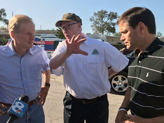 Sen. Bill Nelson, D-Fla., left, and U.S. Sen. Marco Rubio, R-Fla., right, listen to Michael Sparks, the CEO of Florida Citrus Mutual, an industry group, Sept. 13, 2017, in Lake Wales, Fla. The senators toured an orange grove in Lake Wales to assess the scope of damage to the state's iconic crop in the wake of Hurricane Irma.