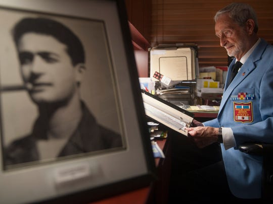 Korean War veteran Stan Levin looks through an album containing some of his old military photographs as he sits near a photo of himself from 1953.