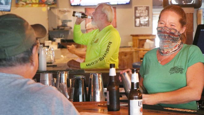 Bartender Angie Potter, chats with a guest while wearing a mask and making drinks, Friday June 5, 2020 as guests can now drink at the bar at the Flagler Tavern in New Smyrna Beach.