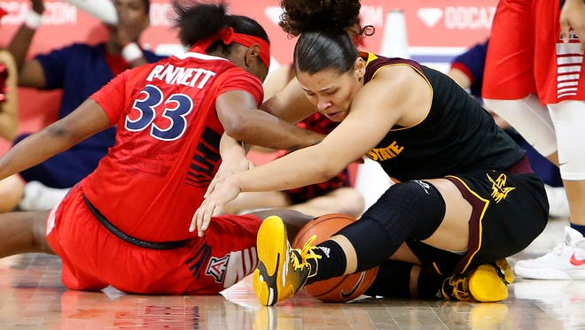 Arizona guard JaLea Bennett (33) and Arizona State guard Sabrina Haines battle for a loose ball during the first quarter of an NCAA college basketball game, Sunday, Jan. 24, 2016, in Tucson, Ariz.