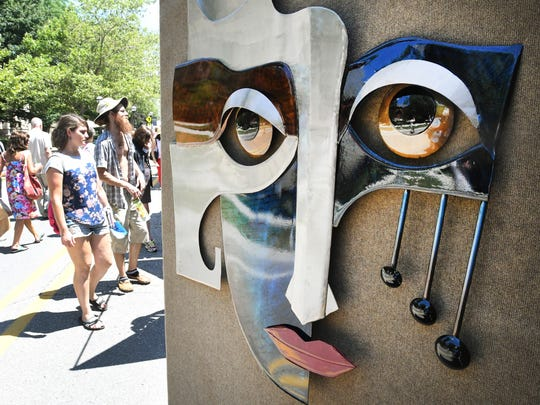 A face, created by Courtney and Rommel Ricaurte of Steel Alive in Lawrenceburg, Tennessee, watches over the crowd passing by at the Ann Arbor Art Fair,
