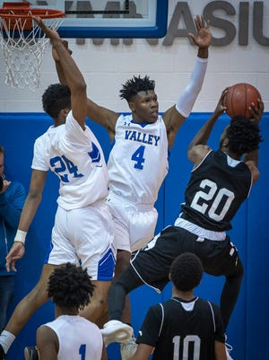 Valley's Curt Lewis (4) and Jerry Davis (24) block the shot of Pleasure Ridge Park's Bryant Robinson (20) during the game at Valley High School in Louisville, Kentucky, Saturday, December 12, 2017