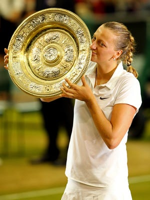 Petra Kvitova of Czech Republic poses with the Venus Rosewater Dish trophy after her Wimbledon victory.
