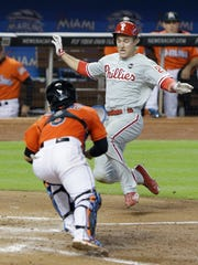 Philadelphia Phillies; Chase Utley, right, slides into home to score on a single by Ryan Howard as Miami Marlins catcher Jhonatan Solano, left, attempts the tag during the seventh inning.