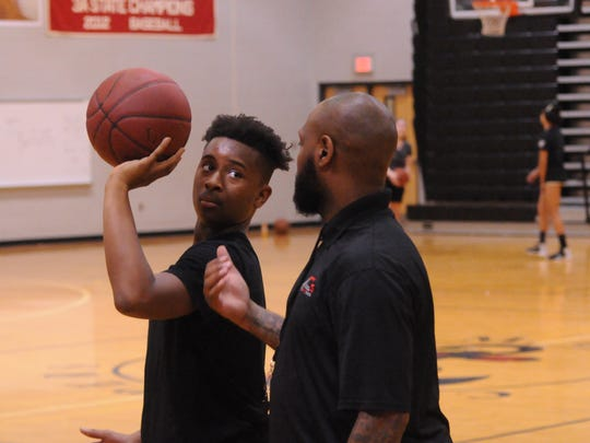 Andre Collins instructs a player on his shot during a basketball clinic at James M. Bennett.