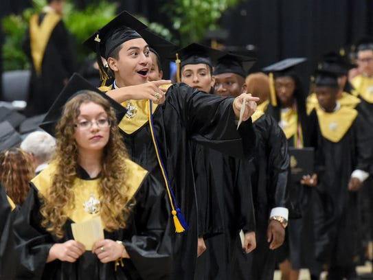 Graduate Guy Gonzalez celebrates with members of the
