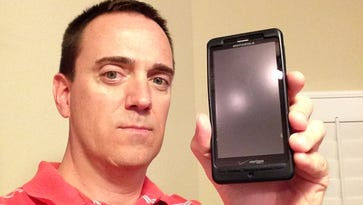 Dave Breitenstein holds the cell phone that defied gravity -- and logic -- at a historic hotel in St. Petersburg.