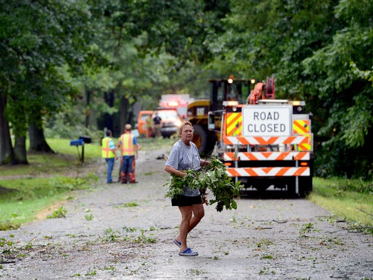 A woman carries debris from her yard to the side of the road as crews from the Ingham County Road Commission clear trees from Green Road, near Shepper Road, in Stockbridge on Wednesday.