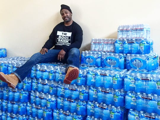 Hamadi Martin sits atop some of the bottled water volunteers have collected for residents of Flint, Michigan.