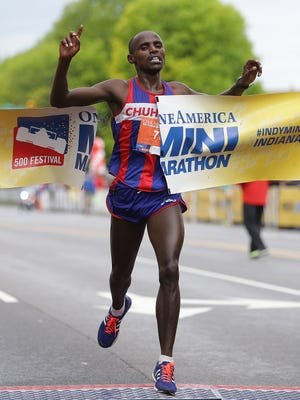John Murugu celebrates his victory in the 500 Festival OneAmerican Mini-Marathon in Indianapolis on Saturday, May 6, 2017. Murugu fnished the half-marathon in 1 hour, 4 minutes, 53 seconds, for the 13.1-mile course
