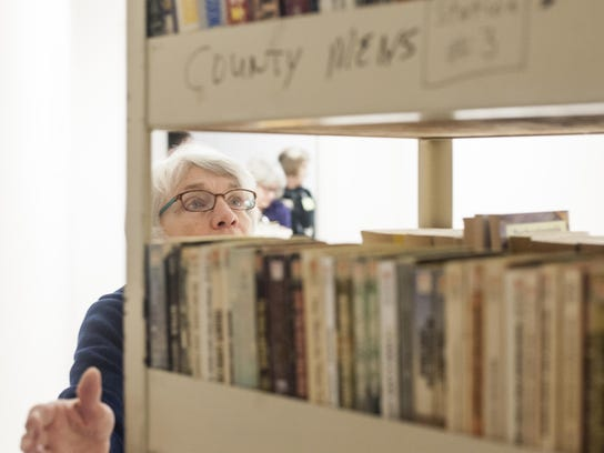 Volunteer Judy Ericksen moves carts of books for inmates