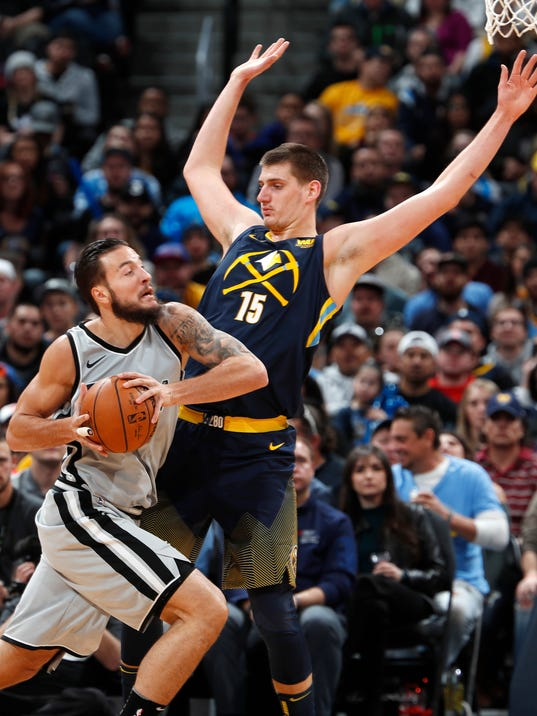 San Antonio Spurs center Joffrey Lauvergne, left, drives against Denver Nuggets center Nikola Jokic on the way to to the basket during the first half of an NBA basketball game Tuesday, Feb. 13, 2018, in Denver. (AP Photo/David Zalubowski)