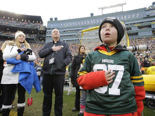 Austin Beauchamp, 6, of De Pere places his hand over his heart during the national anthem before the start of the Green Bay Packers' 38-10 win over the Seattle Seahawks at Lambeau Field.