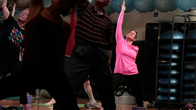 Damian Zynda, 58, of Henrietta, right, joins in a gentle yoga class at the Southeast YMCA in Pittsford.